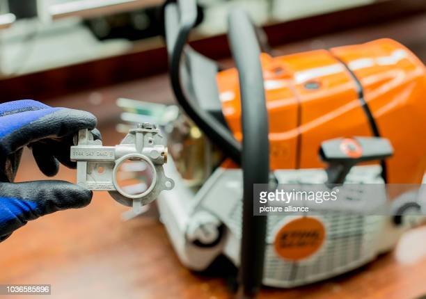 Chainsaw chain stock photos and pictures getty images an employee of chainsaw producer stihl shows a pump to put sticking oil onto the chain greentooth Choice Image
