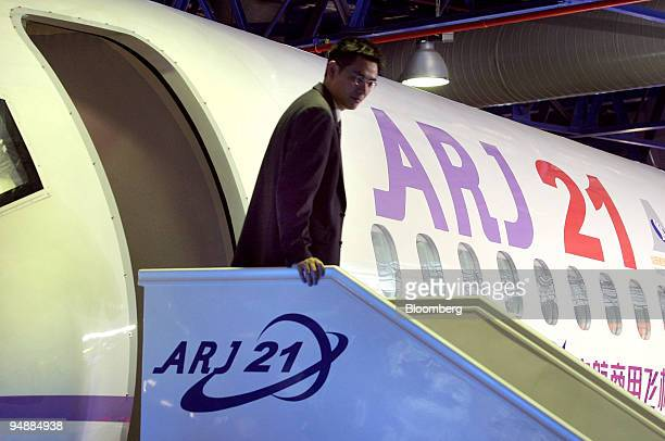 An employee of China Aviation Industry Corp I exits a mockup of the company's ARJ21 regional passenger plane at the Asian Aerospace 2004 show in...