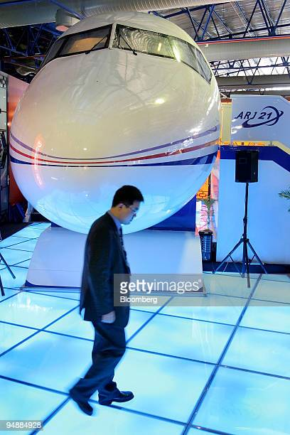 An employee of China Aviation Industry Corp I walks past a mockup of the company's ARJ21 regional passenger plane at the Asian Aerospace 2004 show in...