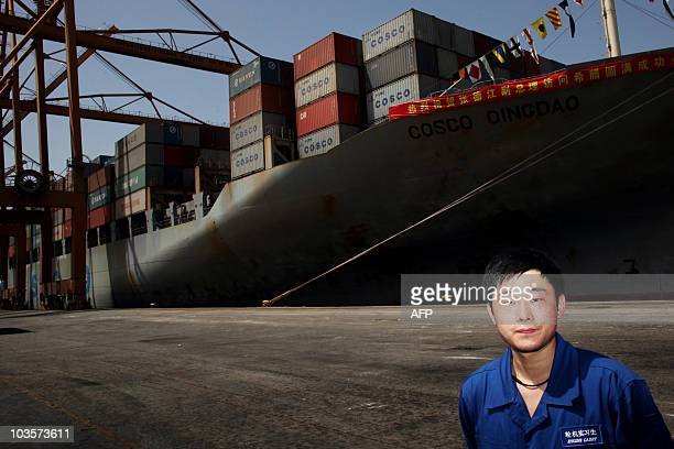 An employee of China Ocean Shipping Company stands in front of the ship Cosco Qingdao, during a visit by China's deputy Prime Minister's Zhang...