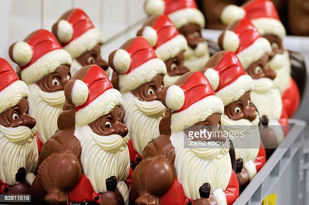 An employee of chocolate manufacturer Fesey packs Santa Claus figures in boxes on December 2 2008 in Riemerling near Munich The chocolate is first...