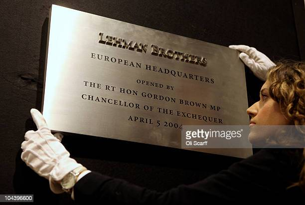 An employee of Christie's auction house adjusts a commemorative plaque from the opening of the Lehman Brothers offices in Canary Wharf, which is...