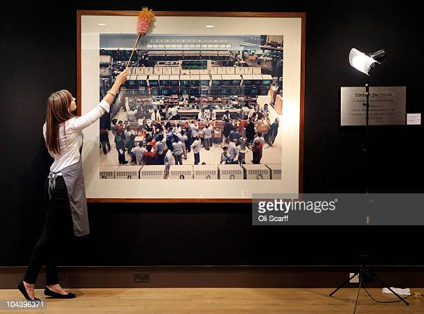 An employee of Christie's auction house cleans a photograph by Andreas Gursky entitled New York Mercantile Exchange which is estimated to sell for...