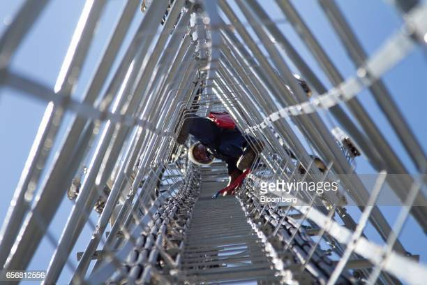 An employee of CJA Telecoms climbs up the inside of an MTN Group Ltd cellular phone mast to perform contract maintenance work in Cape Town South...