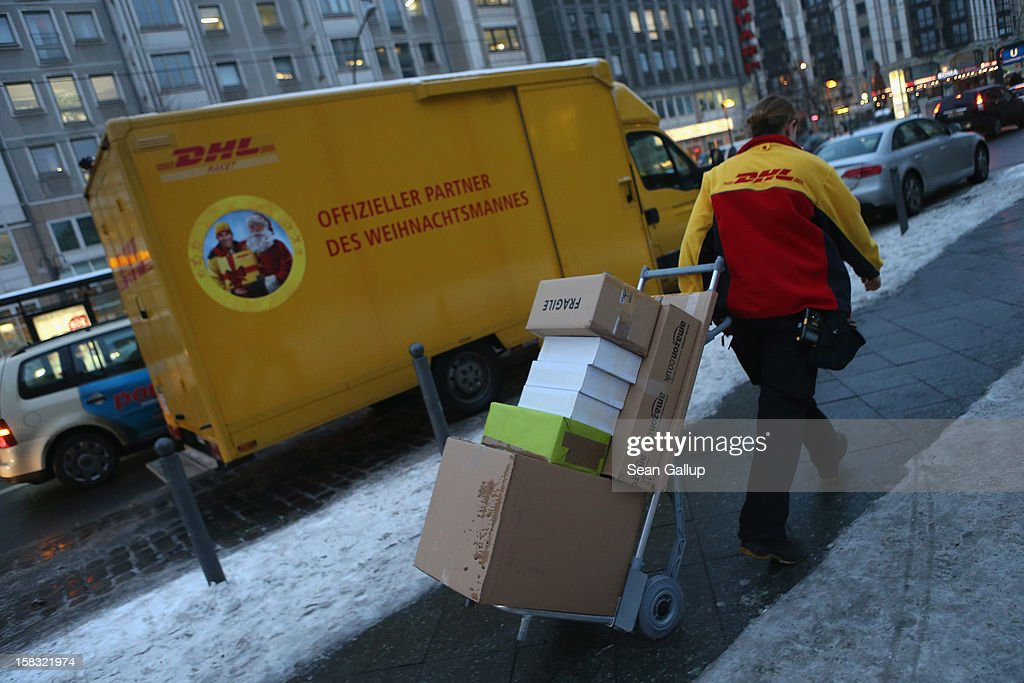 An employee of DHL delivers packages shortly before Christmas on December 13, 2012 in Berlin, Germany. Christmas season is the busiest period for postal and courier deliveries, particularly in recent years as consumer have increased their online gift purchasing volume.