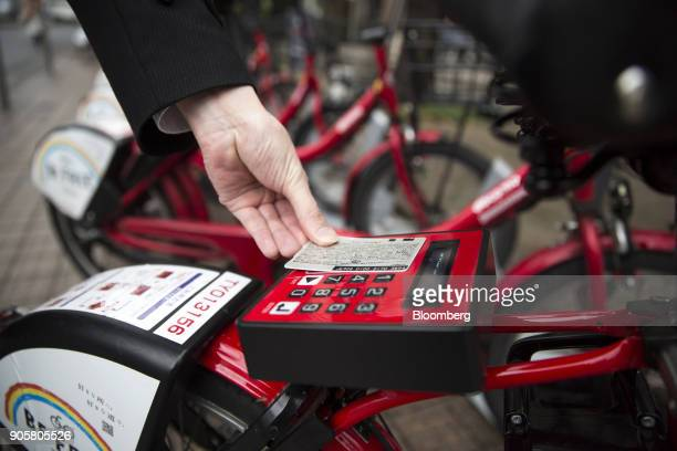 An employee of Docomo Bikeshare Inc a unit of NTT Docomo Inc demonstrates unlocking a rental bicycle at a docking station in Tokyo Japan on Monday...