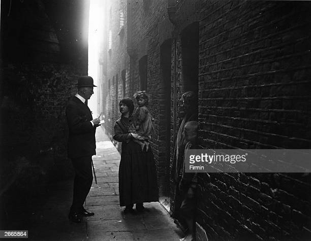 An employee of Dr Barnardo's Homes pays a visit to a poor family in a deprived area of Shadwell in east London December 1920