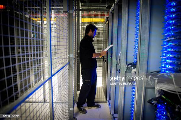 An employee of Equinix data center checks servers on July 21 2014 in Pantin a suburb north of Paris in the SeineSaintDenis department Data centers...