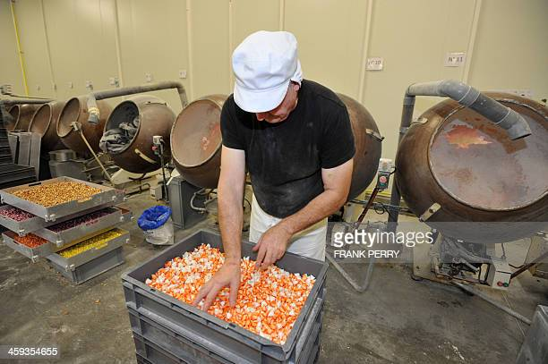 An employee of French candy manufacturer BontePinson looks at 'Berlingots nantais' traditionnal candies on December 13 2013 on the firm's plant in...