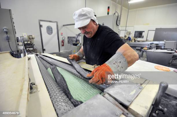 An employee of French candy manufacturer BontePinson works on the preparation of 'Berlingots nantais' traditionnal candies on December 13 2013 on the...