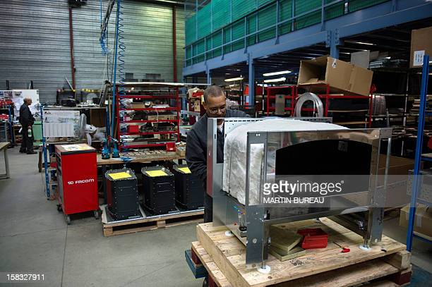 """An employee of French cooker maker """"La Cornue"""" works in the factory on December 13 in Saint-Ouen-l'Aumone, north of Paris. AFP PHOTO / MARTIN BUREAU"""