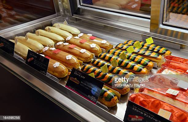 An employee of French food company Fauchon displays a plate of eclairs decorated to symbolise colours of the kabuki and cherry blossoms at their...