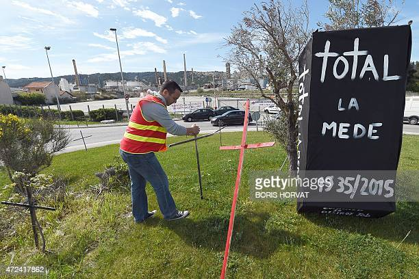 An employee of French oil giant Total's La Mede refinery in ChateauneuflesMartigues southern France puts a wooden cross into the grass on May 7 2015...