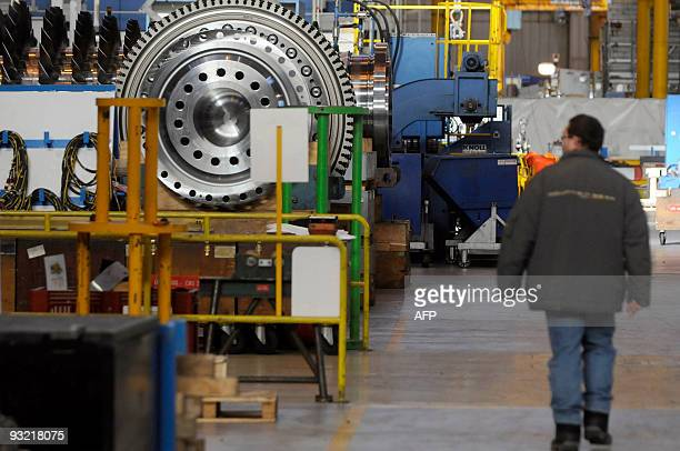 An employee of General Electric passes by a gas turbine at GE Energy Belfort's plant on November 19 2009 GE Energy in Belfort produces medium and...