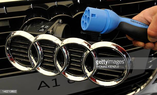 An employee of German car maker Audi demonstrates how to plug in the charging cable at an Audi A1 etron car during the company's annual press...