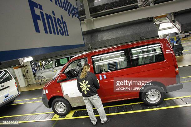 An employee of German car maker Volkswagen checks a T5 Multivan car at the end of an assembly line at the company's commercial vehicle's plant in...