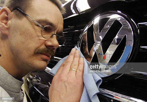 An employee of German car maker Volkswagen polishes the VW logo on a car at the company's commercial vehicle's plant in Hanover, central Germany, 28...
