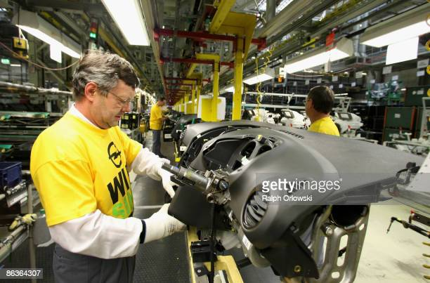 An employee of German carmaker Adam Opel GmbH works on an Opel Corsa at a plant on May 4 2009 in Eisenach Germany Representatives of the German...