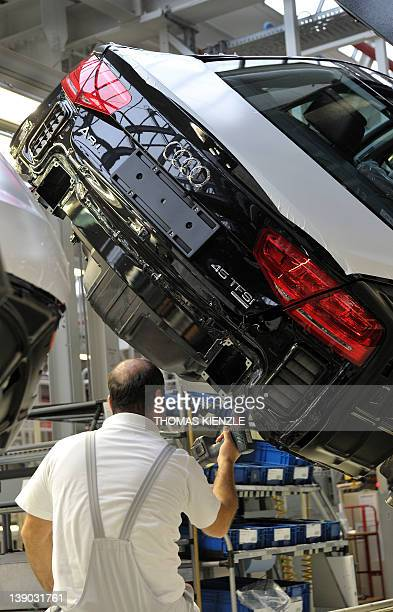 An employee of German luxury car maker Audi works on an Audi A8 car on the assembly line at the Audi plant in Neckarsulm southwestern Germany on...