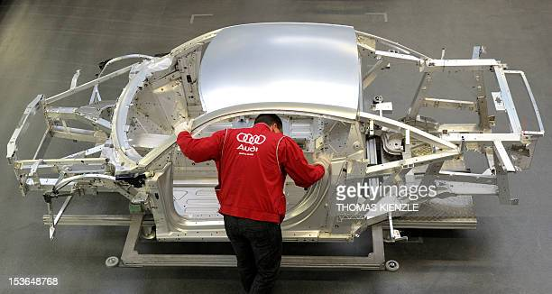 An employee of German luxury car maker Audi works on an Audi R8 sportscar at an assembly line of the Audi plant in Neckarsulm southwestern Germany on...