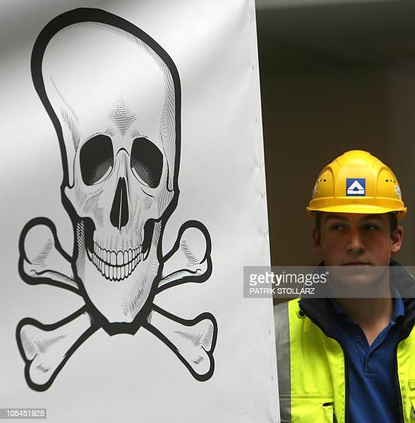 An employee of Germany's largest construction company Hochtief wearing a helmet stands next to a banner with a skull and crossbones inside of their...