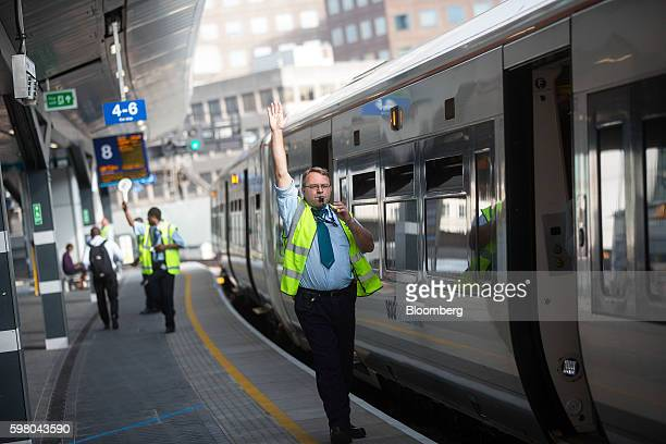 An employee of GoAhead Group Plc's SouthEastern railway franchise blows a whistle to signal for a train to leave from a newly opened platform at...