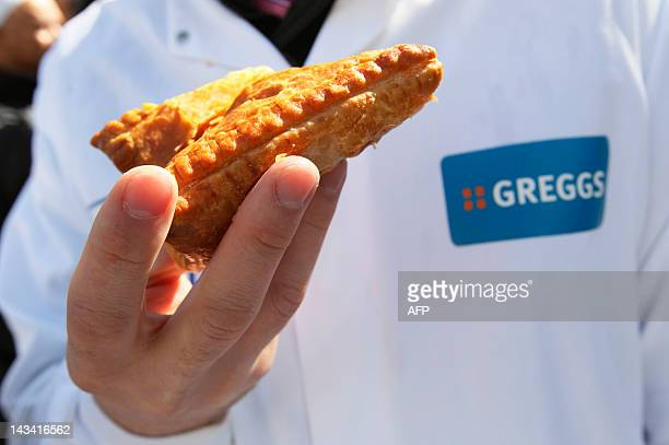 An employee of Greggs bakery holds a pasty as he joins demonstrators outside Downing Street in London on April 26, 2012 to protest and deliver a...