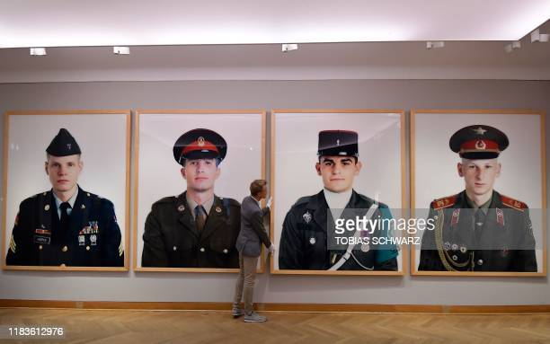 An employee of Grisebach auction house hangs giant photos by photographer Frank Thiel of the Allied soldiers who once patrolled Berlin that have been...