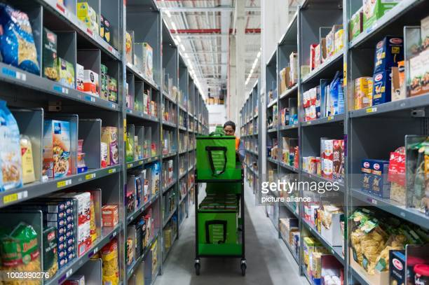 An employee of grocery delivery service Amazon Fresh between two rows of shelves at the company depot in Berlin Germany 18 July 2017 Amazon Fresh...