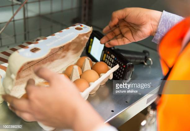 An employee of grocery delivery service Amazon Fresh checks a carton of eggs before delivery at the company depot in Berlin Germany 18 July 2017...