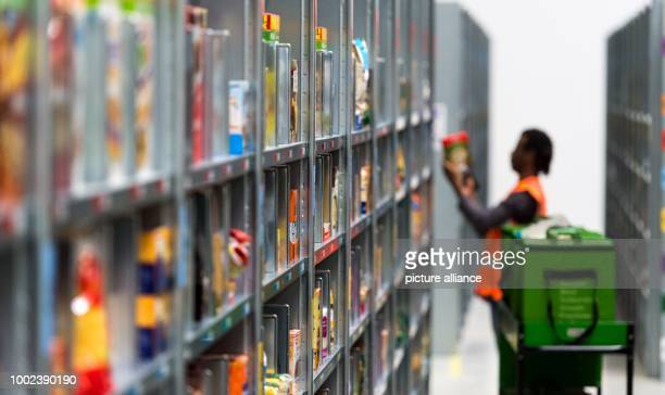 An employee of grocery delivery service Amazon Fresh packs ordered products into a transport bag at the company depot in Berlin Germany 18 July 2017...