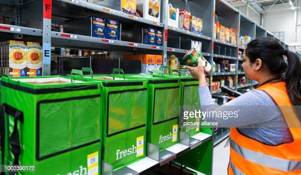 An employee of grocery delivery service Amazon Fresh scans ordered products in the company depot in Berlin Germany 18 July 2017 Amazon Fresh started...