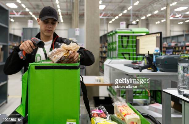 An employee of grocery delivery service Amazon Fresh scans ordered products before putting them into a transport bag at the company depot in Berlin...