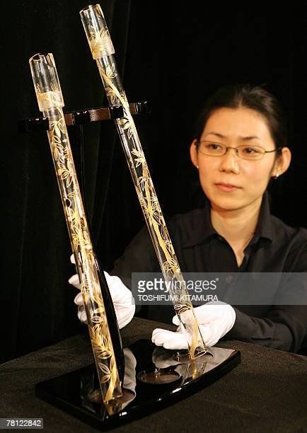 An employee of Hario shows off glassmade Japanese traditional bamboo flutes called a shakuhachi during a press preview at a Tokyo hotel 28 November...