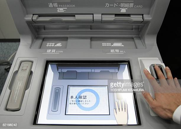 An employee of Hitachi demonstrates the company's latest auto teller machine using a biometric security system to read venous patterns of users'...