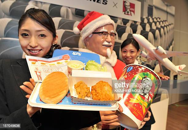 An employee of Japan Airlines shows off a plate of AIR Kentucky Fried Chicken at a press conference to announce their new in flight food service in...