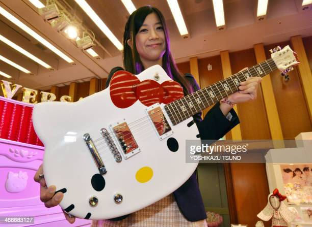 An employee of Japanese character goods maker Sanrio displays a Hello Kitty shaped guitar at an exhibition of Sanrio's products at their headquarters...