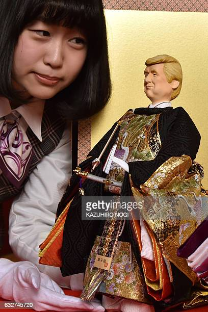 An employee of Japanese doll maker Kyugetsu displays a 'hina' doll with the likeness of US President Donald Trump at the company's showroom in Tokyo...
