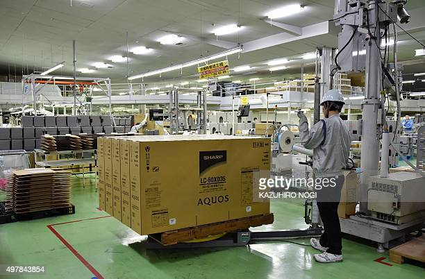 An employee of Japanese electronics giant Sharp carries out packaged AQUOS 4K televisions at the company's Tochigi Plant in Yaita Tochigi prefecture...