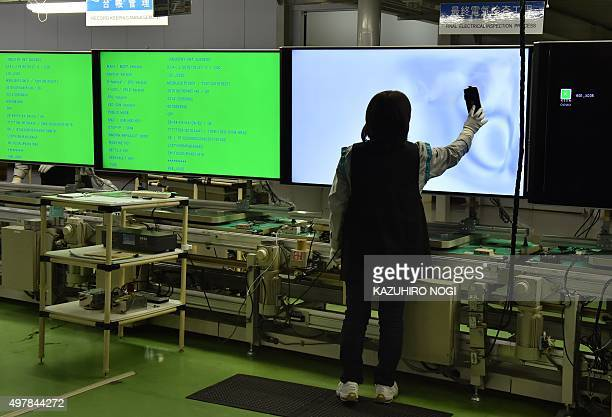 An employee of Japanese electronics giant Sharp performs final electrical inspections on the AQUOS 4K television assembly line at the company's...