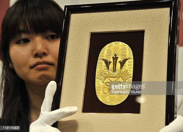 An employee of Japanese jeweller Tanaka Kikinzoku displays a pure gold plate shaped like a large oval gold coin priced 731000 yen at the company's...
