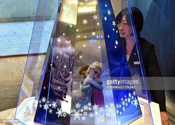 An employee of Japanese jeweller Tanaka Kikinzoku Jewelry displays a 256 million USD Christmas tree made from pure platinum plates with a star...