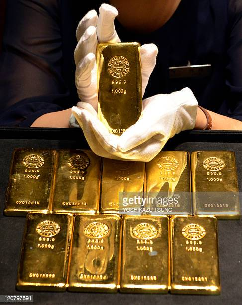 An employee of Japanese jeweller Tanaka Kikinzoku poses with 1kilogram gold bars at the company's main shop in Tokyo on August 11 2011 Gold prices...