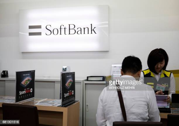 An employee of Japanese mobile telecoms company SoftBank speaks with a customer at a department store in Tokyo on May 10 2017 Japanese mobile...