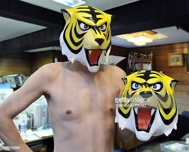 An employee of Japanese toy mask maker Ogawa Rubber wears a rubber mask of the cartoon character Tiger Mask at the company's headquarters in Saitama...