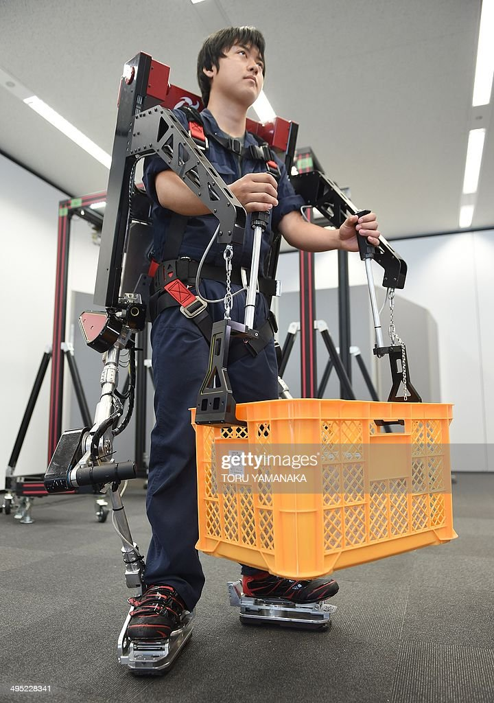 An employee of Japan's Activelink, wearing the company's power assisted POWERLOADER light PLL-01E suit, called 'Ittetsu', lifts a 20 kilo (44 lb.) pack to display its capabilities at a demonstration in Tokyo on June 2, 2014. The company developed the elements to put the 45-kg powered suits into practical use for many industries, such as agriculture, construction, at nuclear plants, for defense, welfare and medical care. AFP PHOTO / Toru YAMANAKA