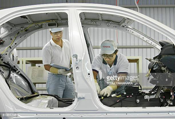 An employee of Japan's auto giant Toyota Motor Corporation checks a process chart when his colleague fits up a seat belt at the Globa Production...