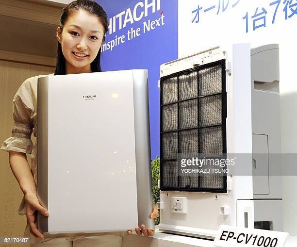 An employee of Japan's electronics giant Hitachi displays the new highperformance air purifier 'Cleair' equipped with various sensors of dust odor...