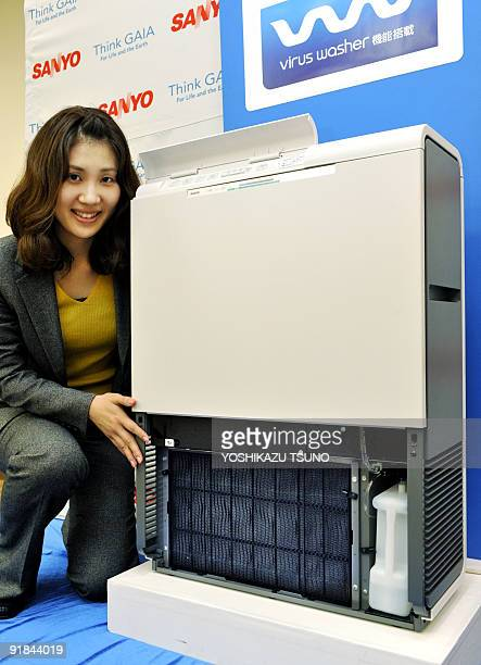 An employee of Japan's electronics giant Sanyo displays the new air purifier for office use the Virus Washer which has a unit with electrolyzed water...