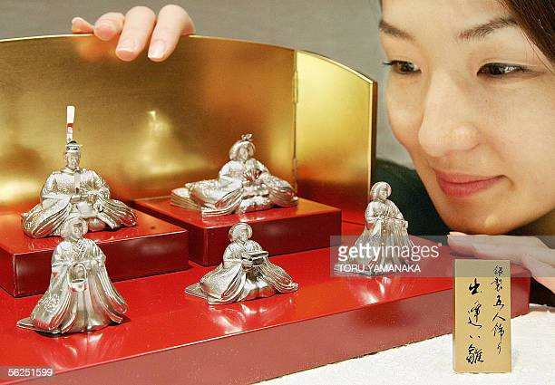 An employee of Japan's Ginza Tanaka admires a set of silver hina dolls displayed in the households on the Girl's Festival day third of March every...